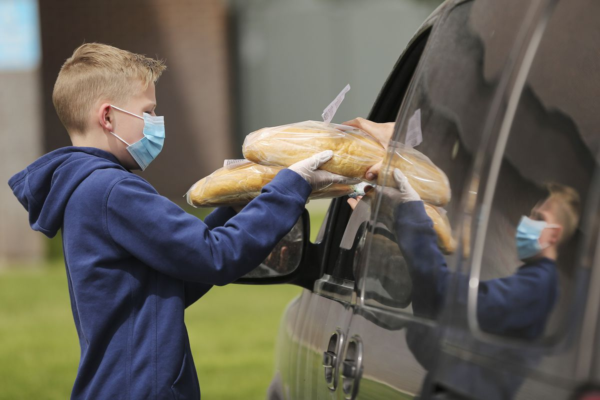 Schmidt's Pastry Cottage volunteer Tyler Bodell hands out two loaves of bread to an area resident at Cyprus High School in Magna during a Free Bread Project giveaway on Sunday, May 17, 2020.