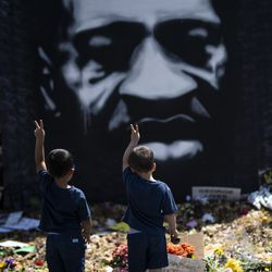 Two boys hold up the peace sign in front of a painting of George Floyd at a memorial site near Cup Foods on June 14, 2020 in Minneapolis, Minnesota.