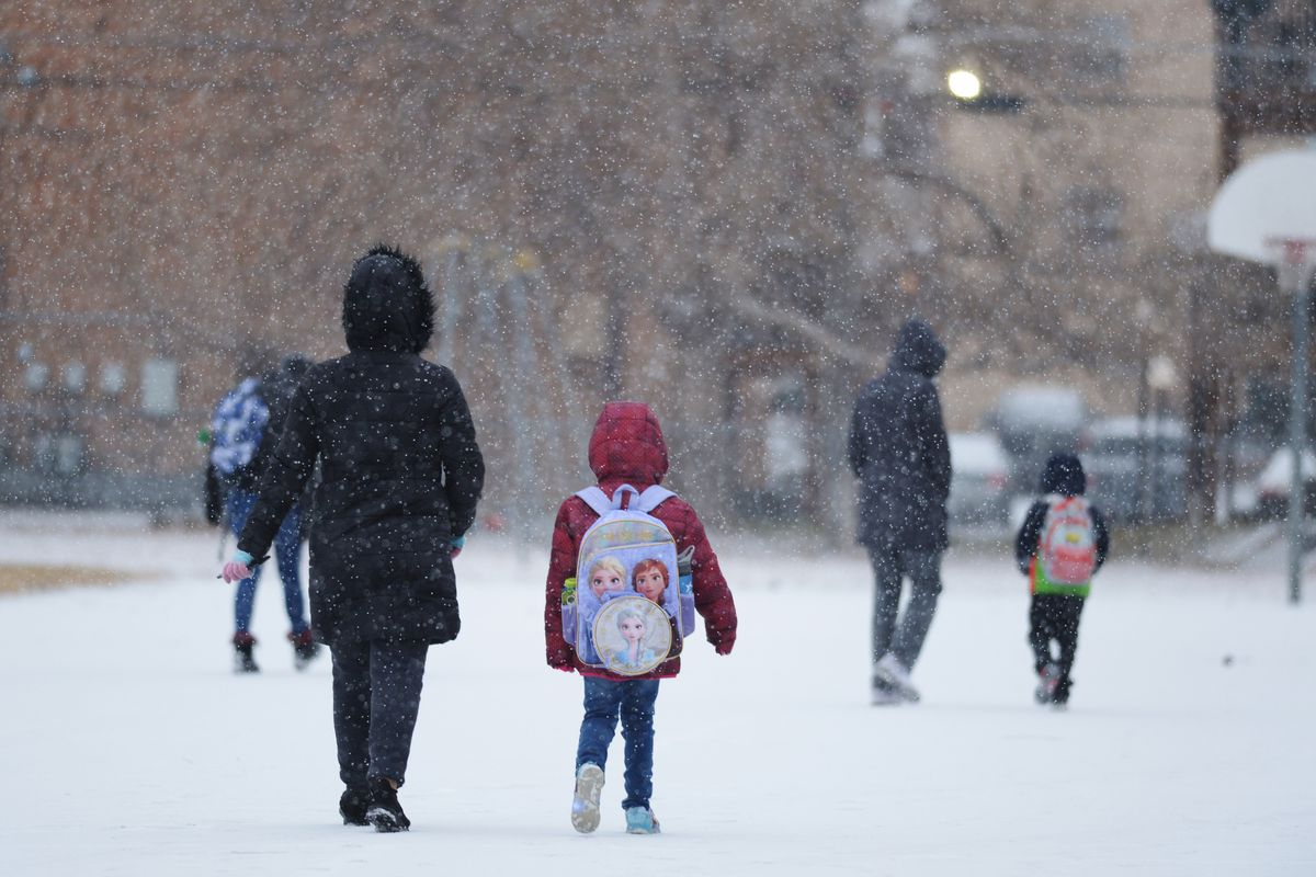 Children wearing winter coats and backpacks walk to school on a snowy day.