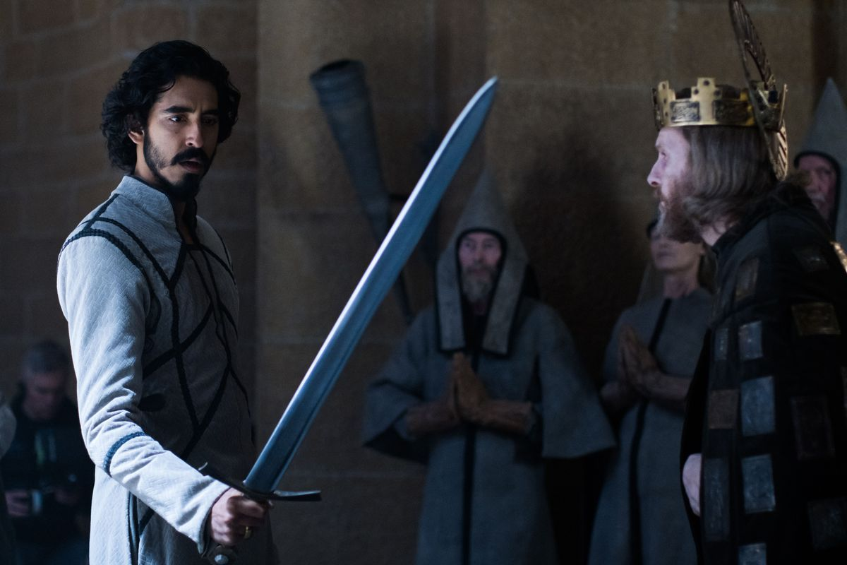 Dev Patel as Gawain holds up Excalibur in court in David Lowery's The Green Knight