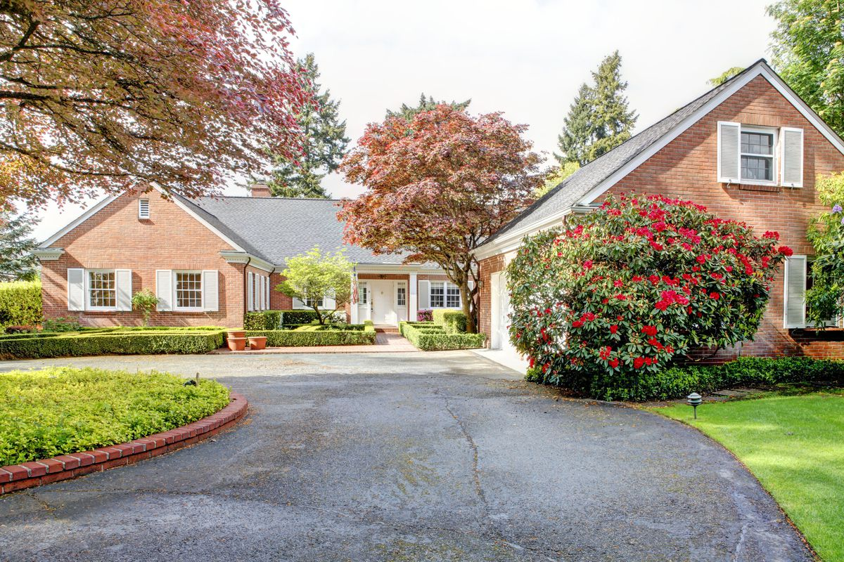 Red brick house with white shutters with green flowering shrubs and long driveway.