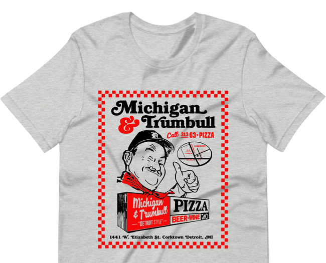 A gray t-shirt with a man wearing a Detroit ball cap giving a thumbs up below a Michigan and Trumbull logo and illustration of the restaurant. It also has the restaurant's phone number and address.