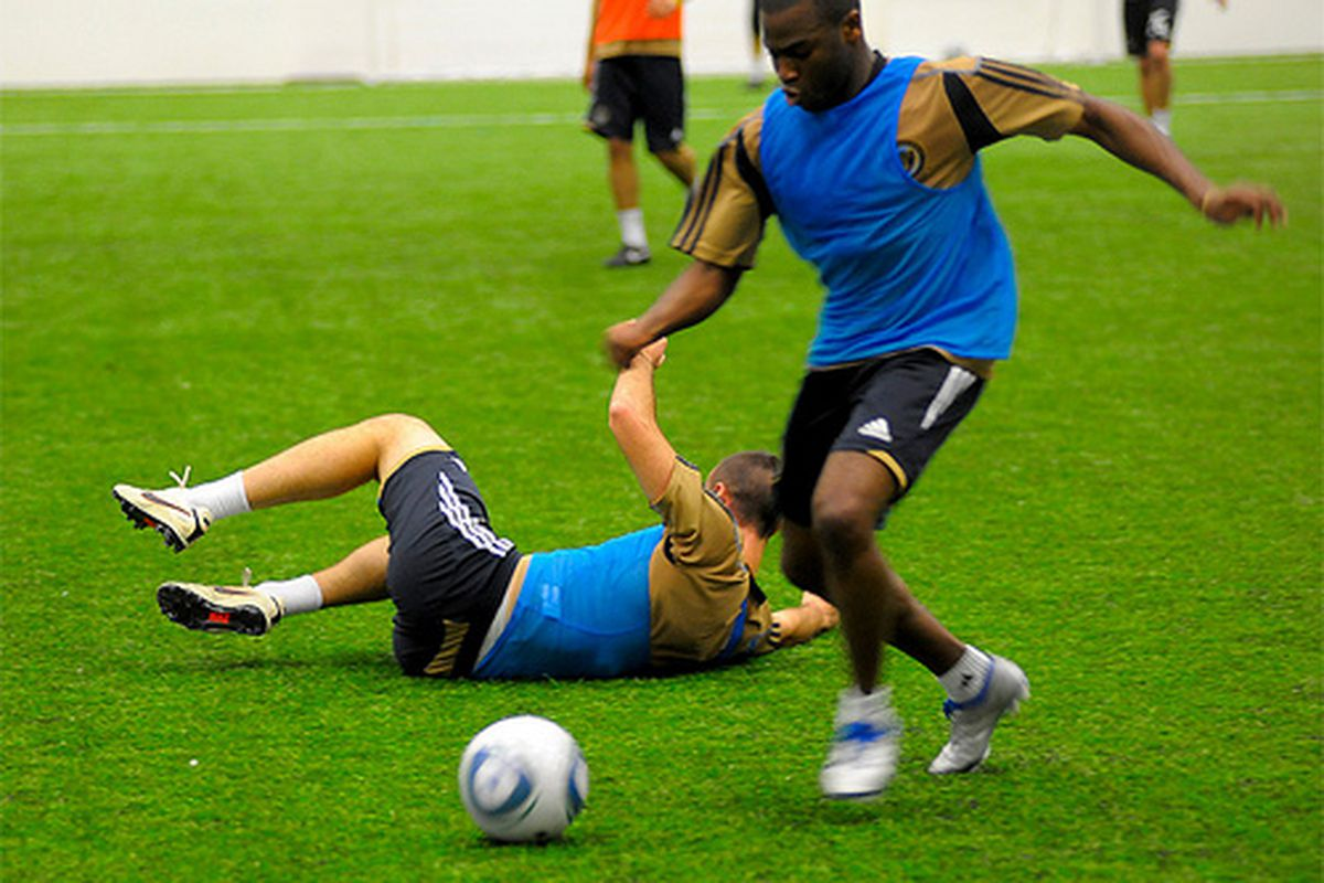 """Chris Agorsor, then only a trialist for the Philadelphia Union, dribbles past the downed Andrew Jacobson. (Photo by <a href=""""http://www.flickr.com/photos/earl_gardner/5398634014/sizes/m/in/set-72157625806401397/"""" target=""""new"""">Earl Gardner</a>)"""