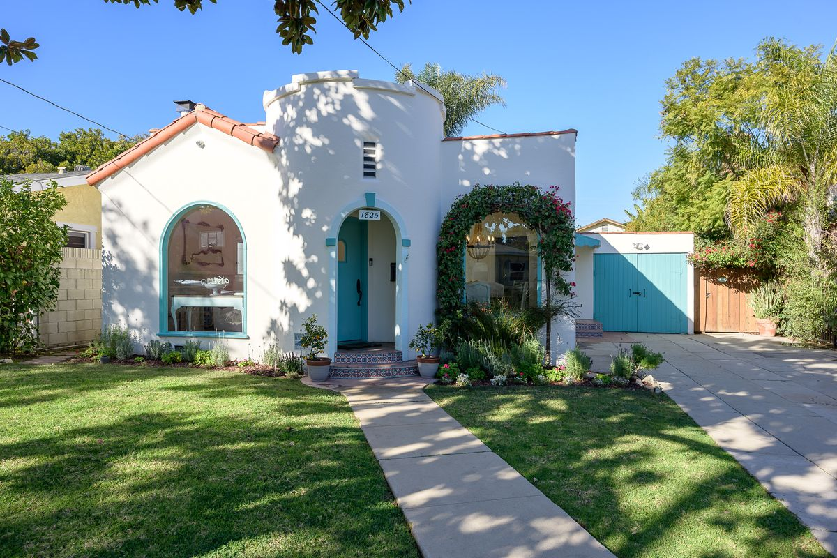 The exterior of a white stucco home with a tower, arched windows, and a tile roof. The trim is painted turquoise.