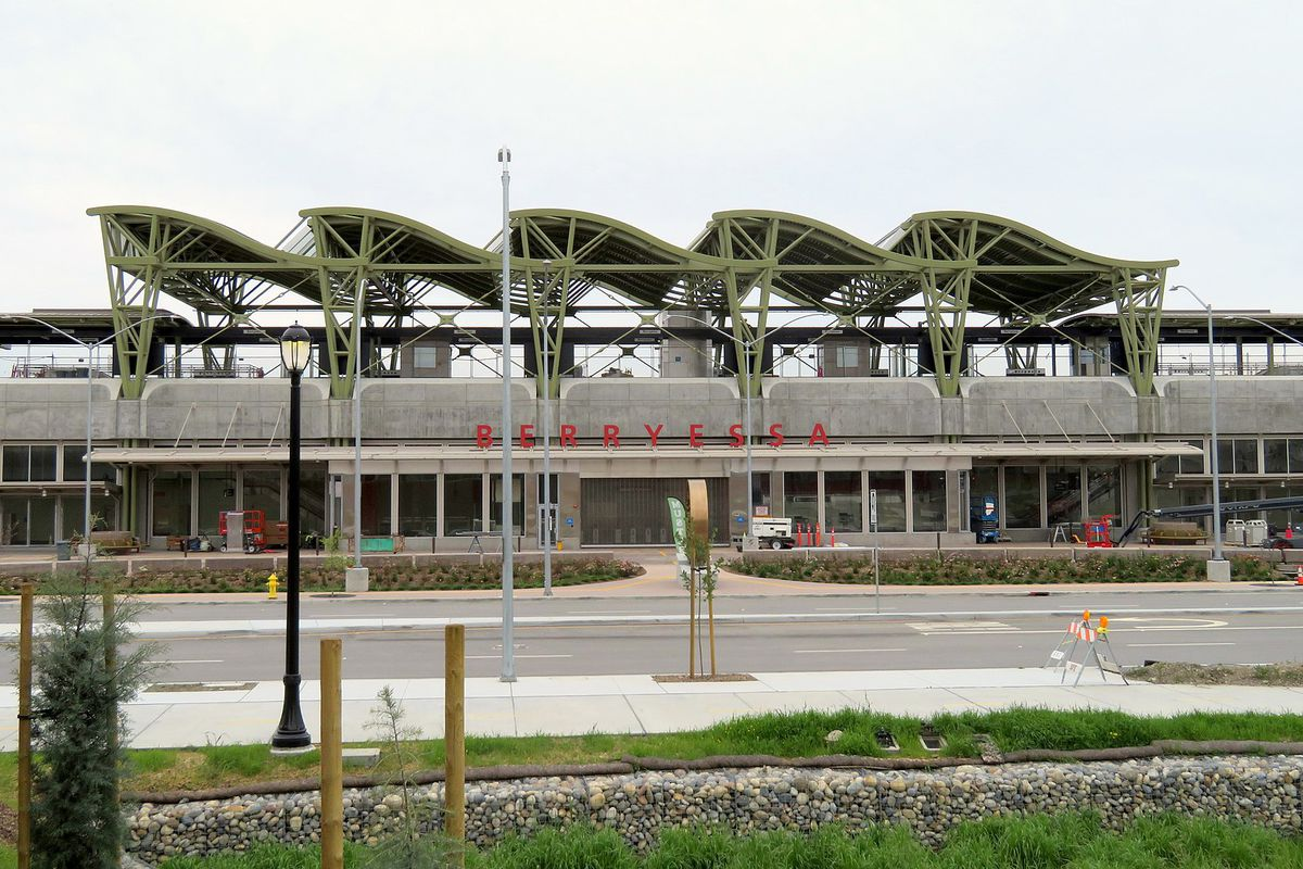 """An under-construction train station, with red lettering reading """"Berryessa."""""""