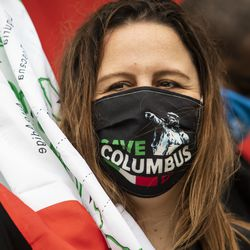 """Madia Crudele, 46, of Harwood Heights, wears a """"Save Columbus Day"""" mask and waves an Italian flag during the Columbus Day: Italian American Heritage Celebration at Arrigo Park in the Little Italy neighborhood, Monday morning, Oct. 12, 2020."""