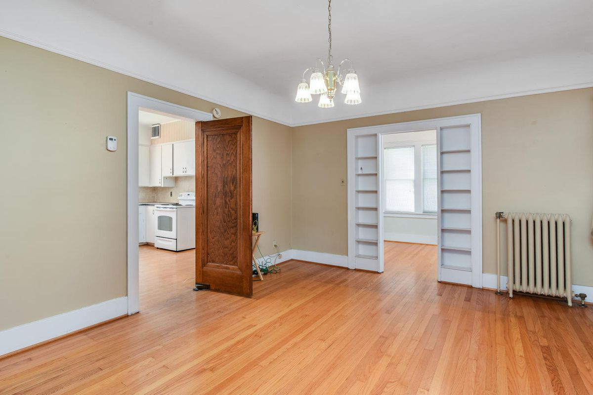 An empty room with narrow built-in shelves around an entryway to another room.