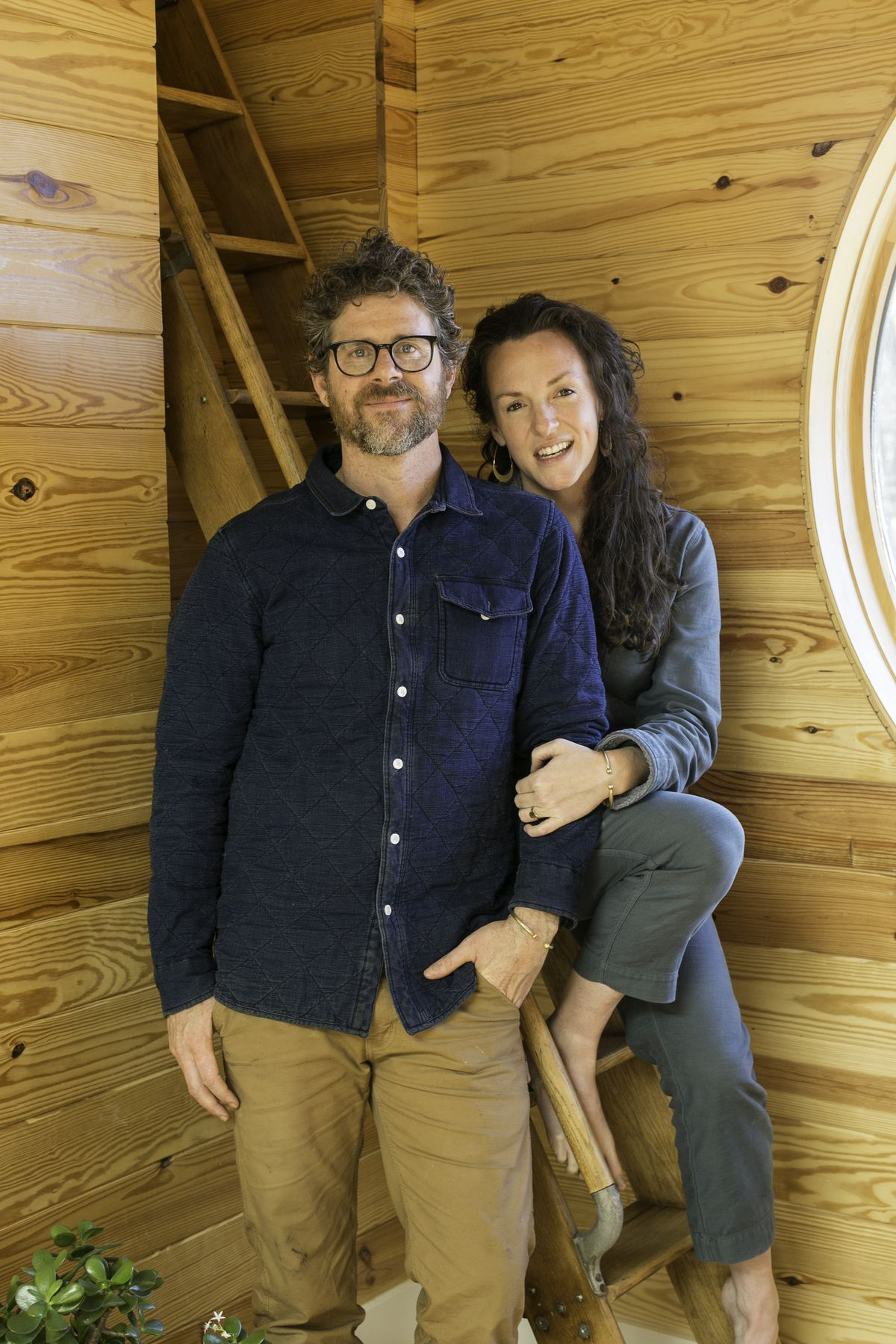 Ross Smith and Anna Welton, the homeowners, in the foyer of their home, paneled wood, and a circular window.