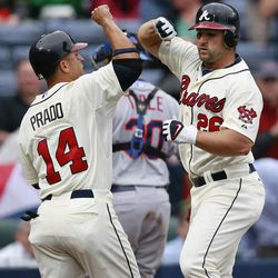Atlanta Braves' Dan Uggla, right, celebrates with Martin Prado after they both scored on an Uggla's two-run home run in the third inning of a Major League Baseball game against the New York Metsin Atlanta, Wednesday, April 18, 2012.