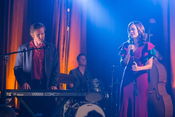 A band is playing music on the stage at an event venue. There are colorful lights. The woman is wearing a red dress. There is a male keyboard player and a male drummer.