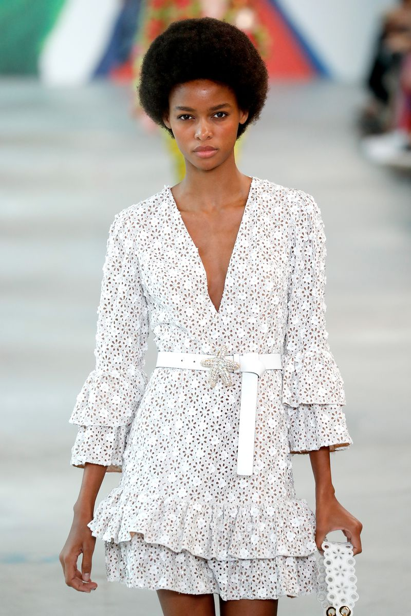 A model wears a frilly white minidress with long bell sleeves.