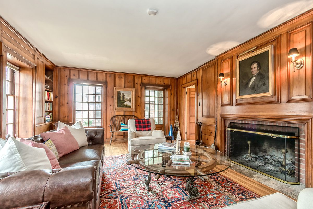 A couch sits across from a long fireplace with just ashes. Every wall has wood paneling.