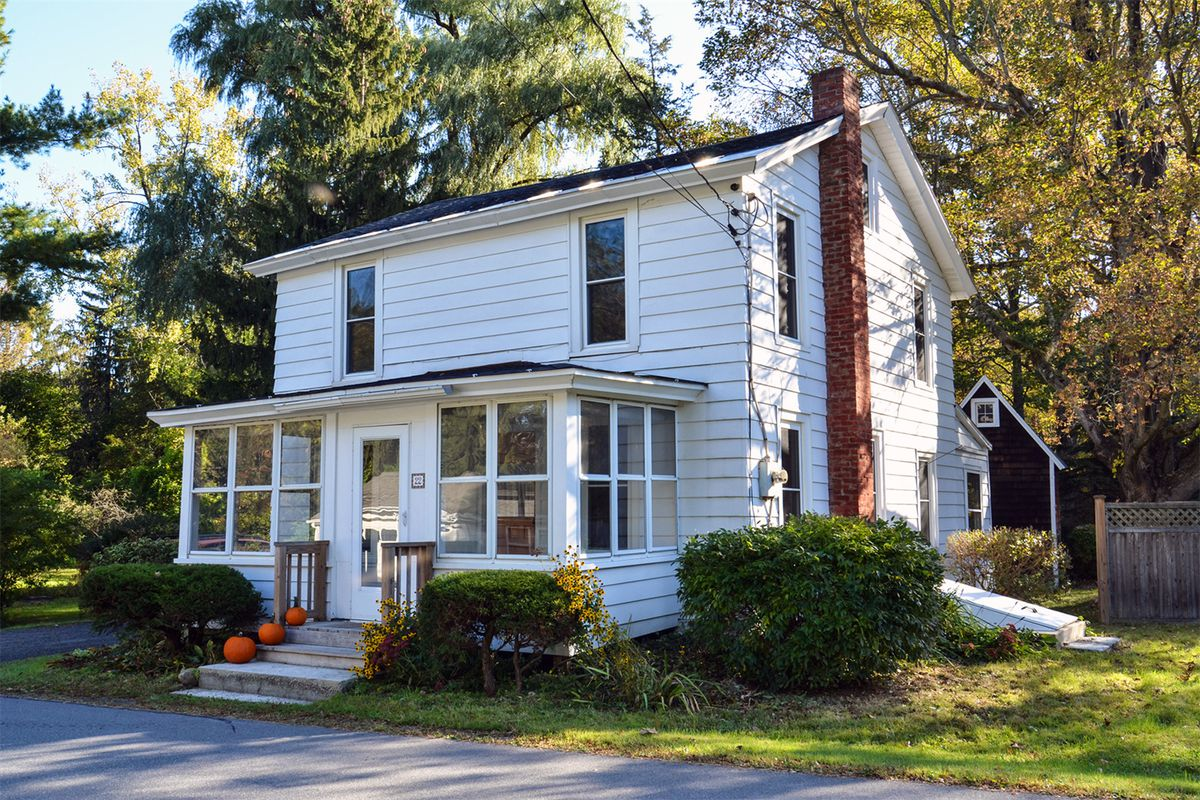 White two-story farmhouse with brick side chimney and front enclosed porch.