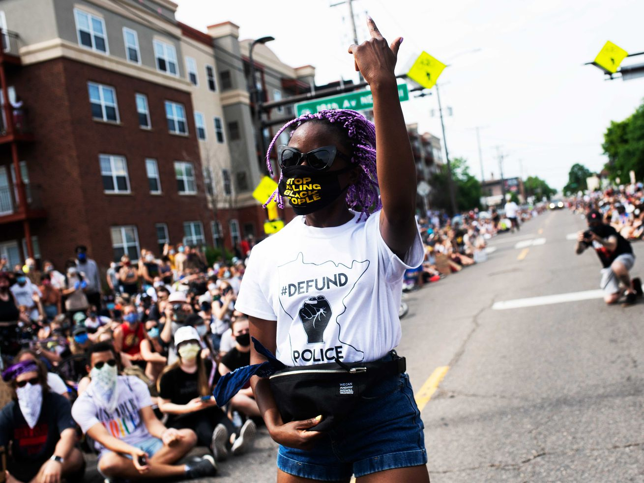 """A woman wearing a mask and a whiteT-shirt reading""""defendthepolice"""" walksdown the street along with many other protestersinMinneapolis"""