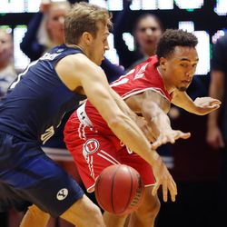 Utah Utes guard Brandon Taylor (11) swipes at the ball as he defends Brigham Young Cougars guard Chase Fischer (1) as Utah and BYU play in the Huntsman Center in Salt Lake City Wednesday, Dec. 2, 2015. Utah won 83-75.