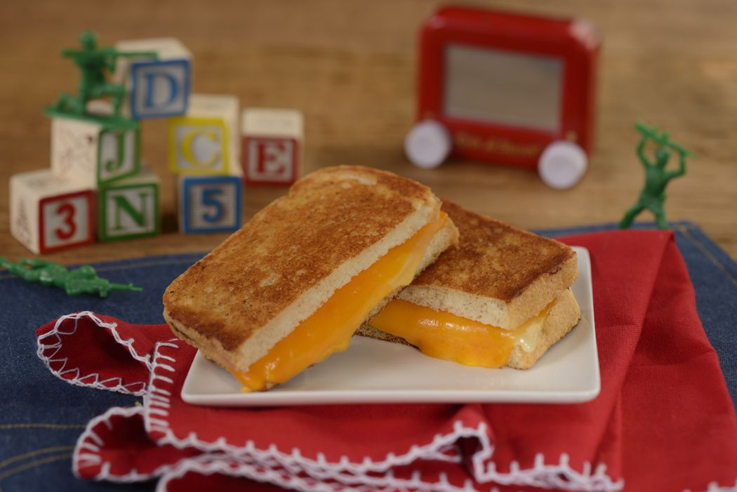 A sliced grilled cheese on a plate in front of children's blocks and other toys