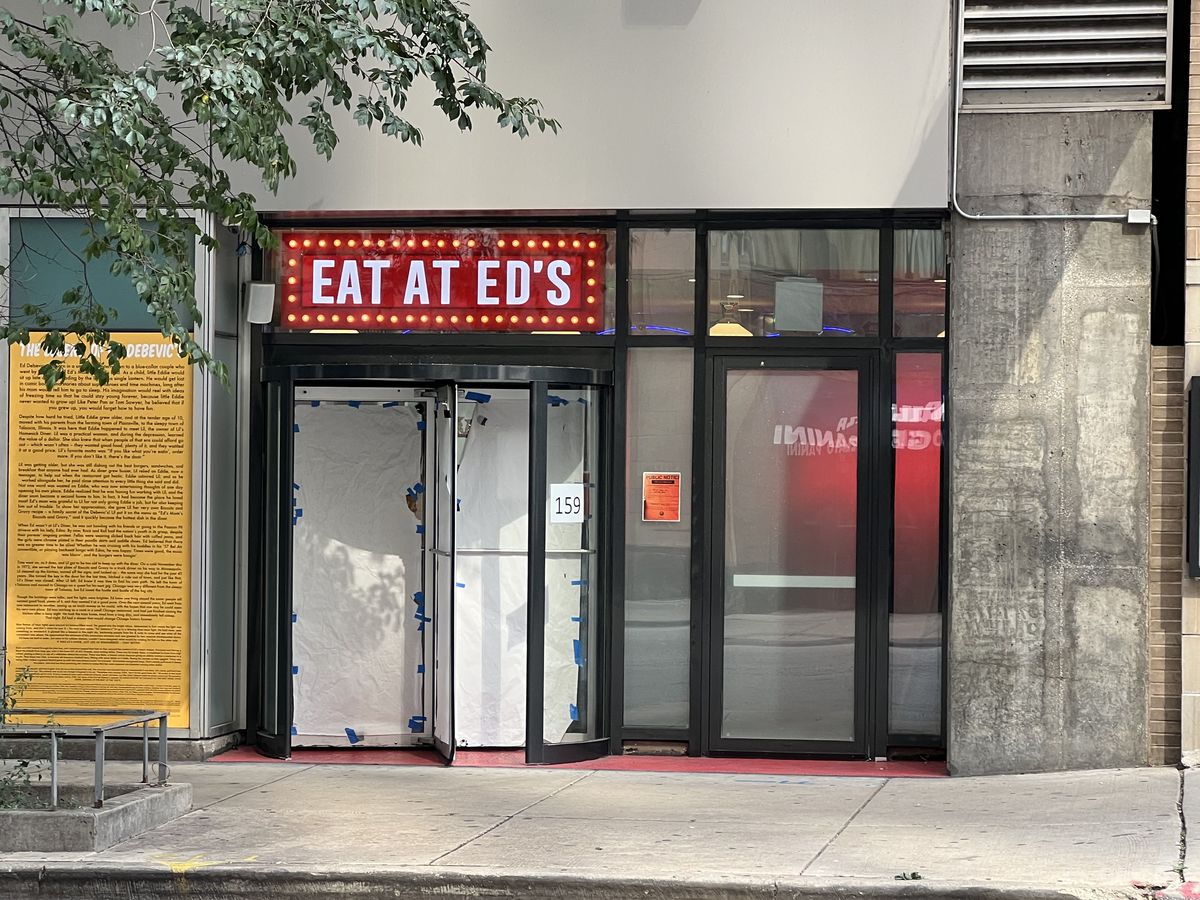 """A storefront restaurant with a large sign over the front doors that reads """"Eat at Ed's."""""""
