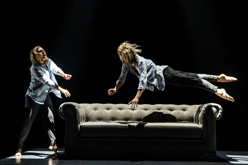 Two blonde women, both dressed identically, are onstage. One is singing and reaching towards the other, who is suspended mid-leap, about to land on a couch.