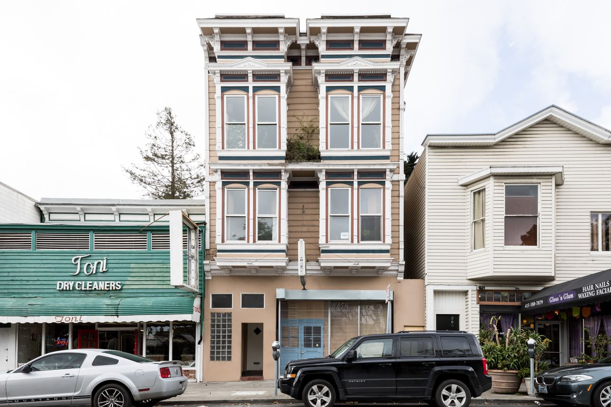 The exterior of a house on Noe Street in San Francisco. The facade is tan with white decorative details.