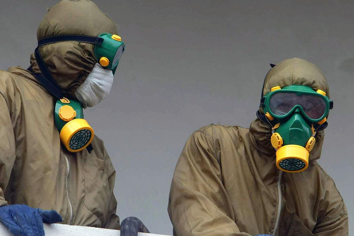 Two Vietnamese soldiers stand on a balcony of the French hospital in Hanoi, 2003, as they prepare to spray disinfectant in rooms on the first floor of the facility considered the centre of the SARS outbreak in Vietnam.