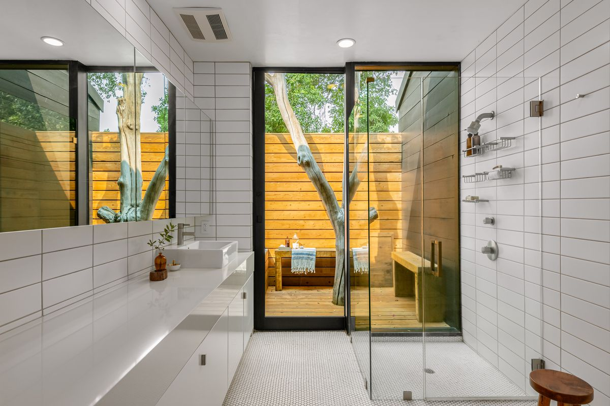 Bathroom with white tile and glass shower.