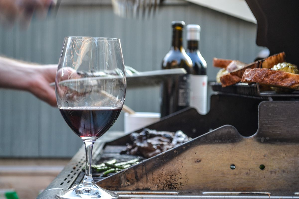 A glass of red wine sits near a grill where someone is cooking a variety of meats