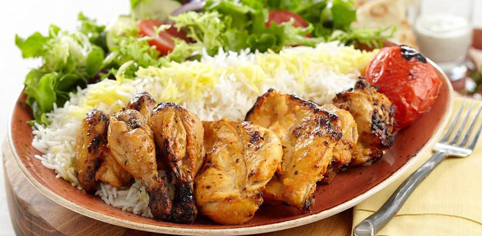 Chicken kabob with basmati rice in the middle of the plate and a salad in the background