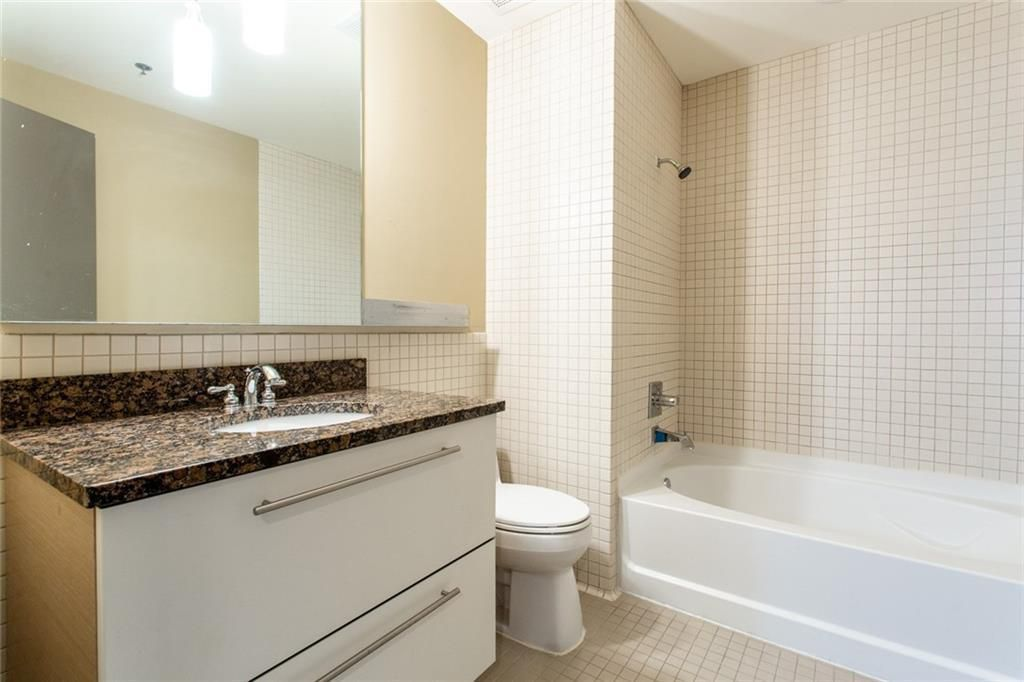 Bathroom with single vanity, toilet and tub/shower combo.