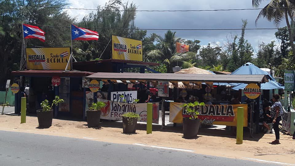 A roadside restaurant and outdoor covered seating area with advertisements and Puerto Rican flags flying