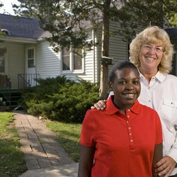 In an Aug. 28, 2012 photo, Sarah Cain, 14, and her mother Susan Cain pose outside their home near Freeport, Ill. Sarah designed postcards to sell to raise money to buy children's books for kids in Haiti, where she was adopted from as an infant.