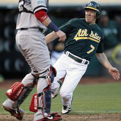 Oakland Athletics' Brandon Inge (7) slides into home plate to score a run past Boston Red Sox catcher Jarrod Saltalamacchia (39) in the third inning of a baseball game Saturday,  Sept. 1, 2012 in Oakland, Calif.