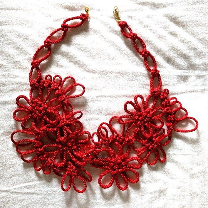 A necklace made up of a red cord manipulated to form the shape of multiple flowers.