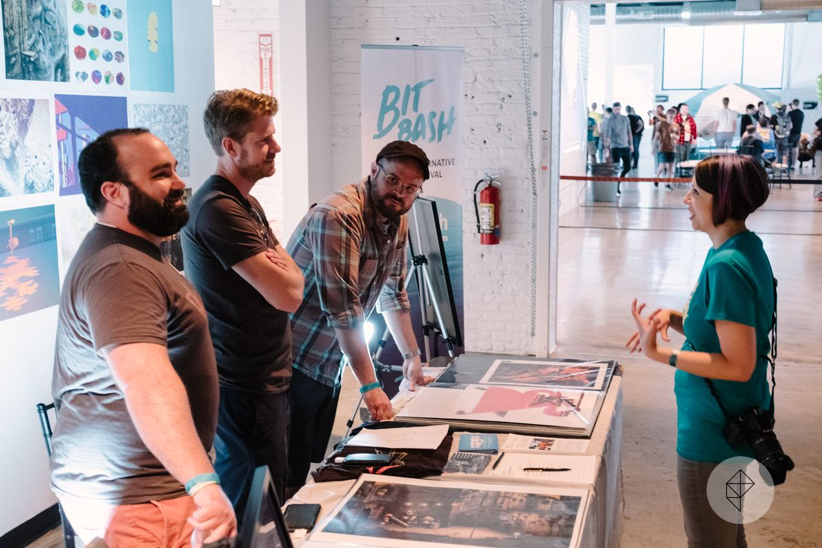 One of the organizers of Bit Bash converses with the staff running the art table.
