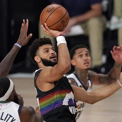 Utah Jazz's Royce O'Neale, left, and Jordan Clarkson, right, defend against a shot attempt by Denver Nuggets' Jamal Murray (27) during the first half an NBA first round playoff basketball game, Tuesday, Sept. 1, 2020, in Lake Buena Vista, Fla.