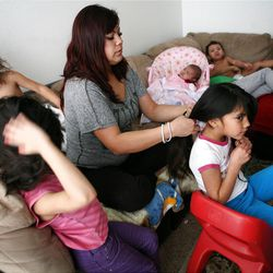 Adriana Carreon, center, braids her daughter Mariza's hair as Mia, left, brushes her mother's hair at home in Taylorsville on Saturday, Feb. 9, 2013. In the foreground is Juliza Carreon. In the background is Adriana Carreon, 2 months, Ariza Carreon and Antonio Carreon. Carreron's family was recently evicted, but they managed to land on their feet.