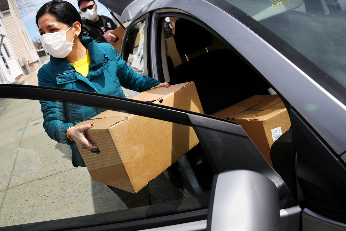 A woman loads food packages into a car in Boston to deliver them to vulnerable immigrant families.