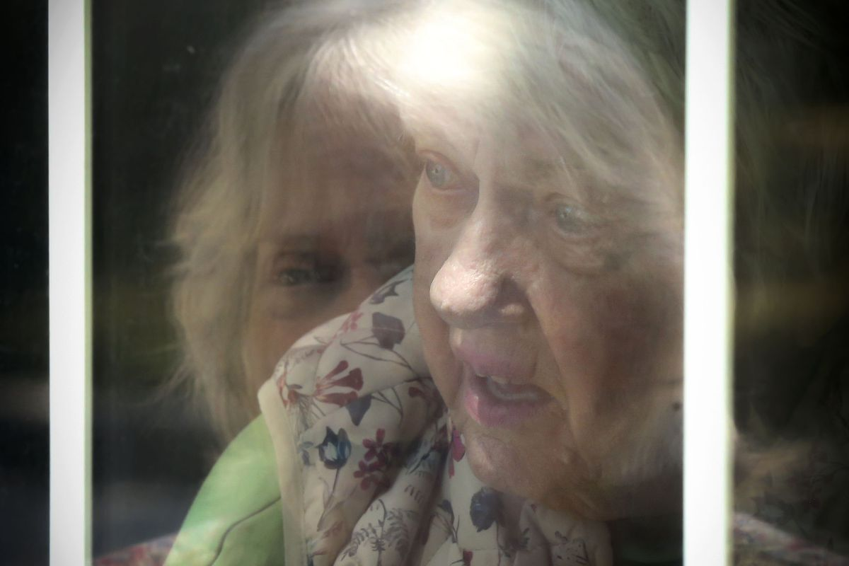 Nita Lutes, a resident at Pacifica Senior Living in Millcreek, speaks through a window with Cathy Chambless on Wednesday, April 29, 2020.