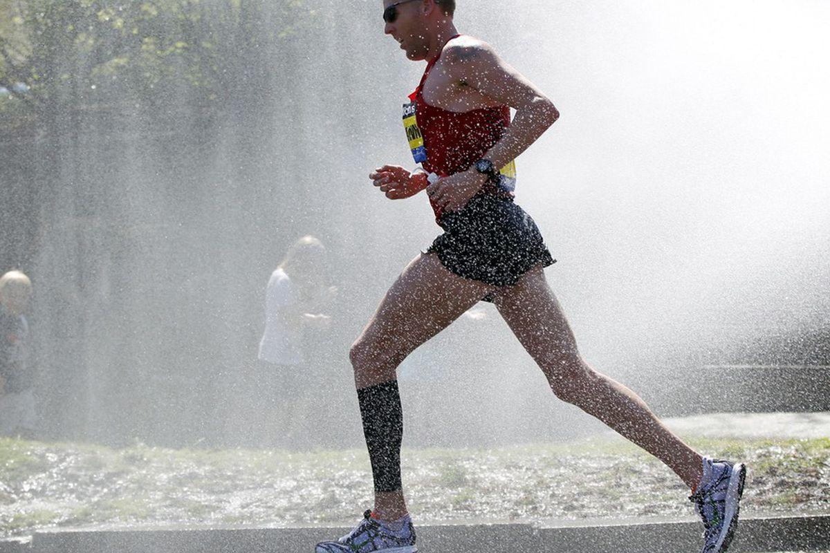 April 16, 2012; Newton, MA, USA; Jason Hartmann (USA) runs thorough water spray near the 19 mile marker during the 2012 Boston Marathon.  Mandatory Credit: Greg M. Cooper-US PRESSWIRE