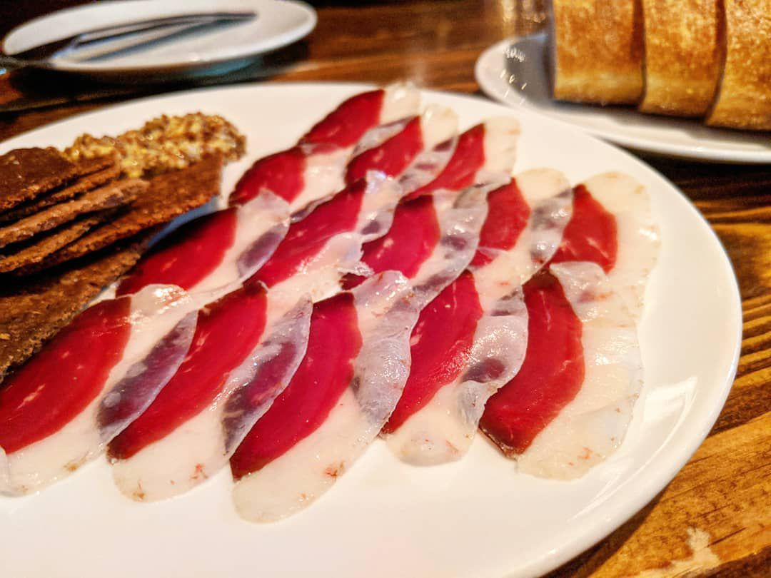 Thinly sliced prosciutto —distinctly bright red with a thick, fatty, white edge —lines a plate, which also has some grainy crackers on it. In the background, there's a plate of sliced bread. The table is wooden.