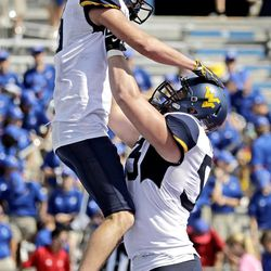West Virginia wide receiver David Sills V, left, and offensive lineman Colton McKivitz (53) celebrate after Sills scored a touchdown during the second half of an NCAA college football game against Kansas, Saturday, Sept. 23, 2017, in Lawrence, Kansas. West Virginia won 56-34.