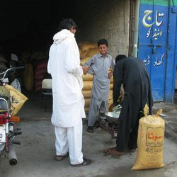 In this Tuesday, Sept. 4, 2012 photo, Pakistani customers from the tribal area of Waziristan buy fertilizer at a shop in Bannu, Pakistan. Pakistan's efforts to cut off the flow of fertilizer to militants using it to make bombs in a key tribal sanctuary along the Afghan border has outraged local farmers, who complain the policy has failed to stymie insurgents but has cut their crop yields in half.