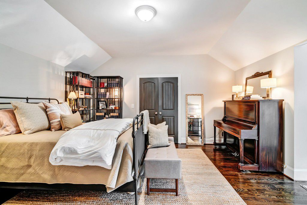 A white attic space with a bedroom in it.