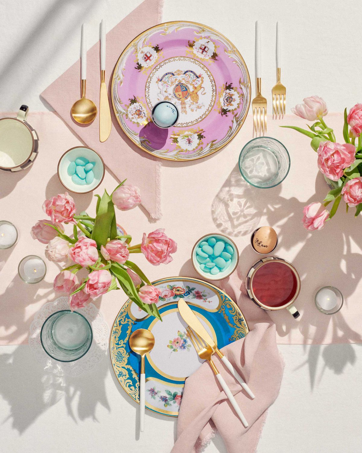 An overhead view of colorful plates with gold and white flatware.