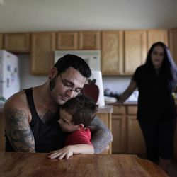 In this Monday, Aug. 1, 2011 photo, Bryon Widner hugs his 4-year-old son, Tyrson, at their home as his wife Julie watches. After getting married in 2006, the couple, former pillars of the white power movement (she as a member of the National Alliance, he a founder of the Vinlanders gang of skinheads) had worked hard to put their racist past behind them. They had settled down and had a baby; her younger children had embraced him as a father.