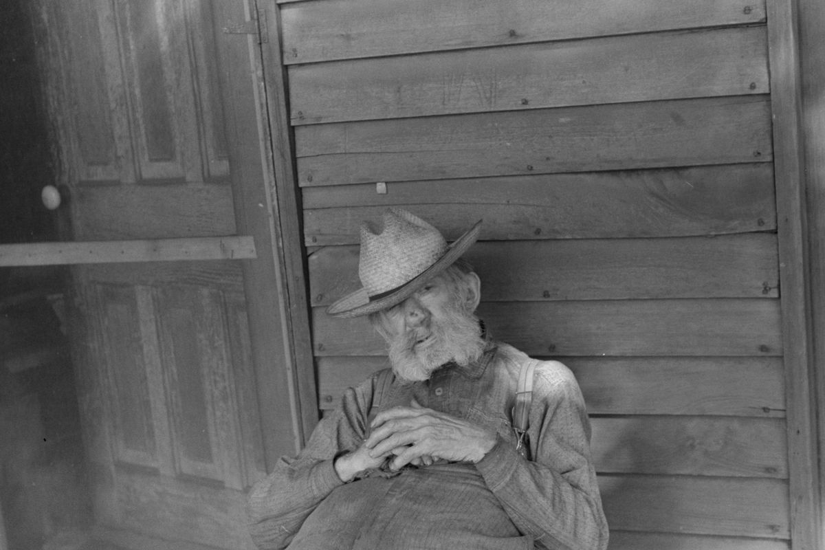 Ex-farmer resting by a house in Circleville,1938