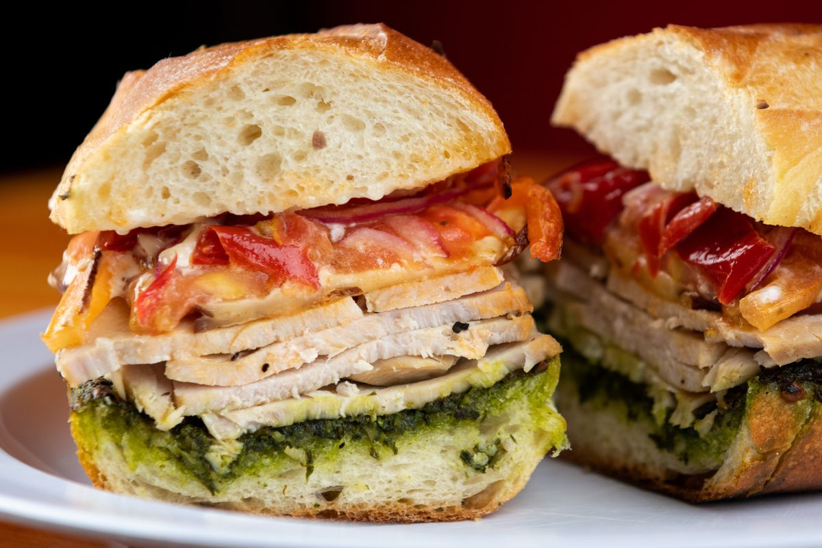 A closeup of a turkey sandwich, with pesto, smoked gouda, and Mama Lil's peppers on a demi baguette