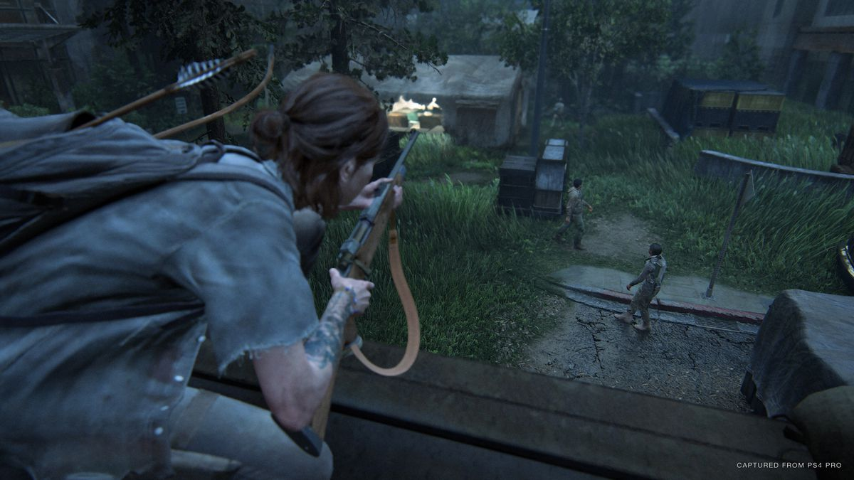 Positioned on a roof in The Last Of Us Part II, Ellie watches people down below, a rifle in her hands.