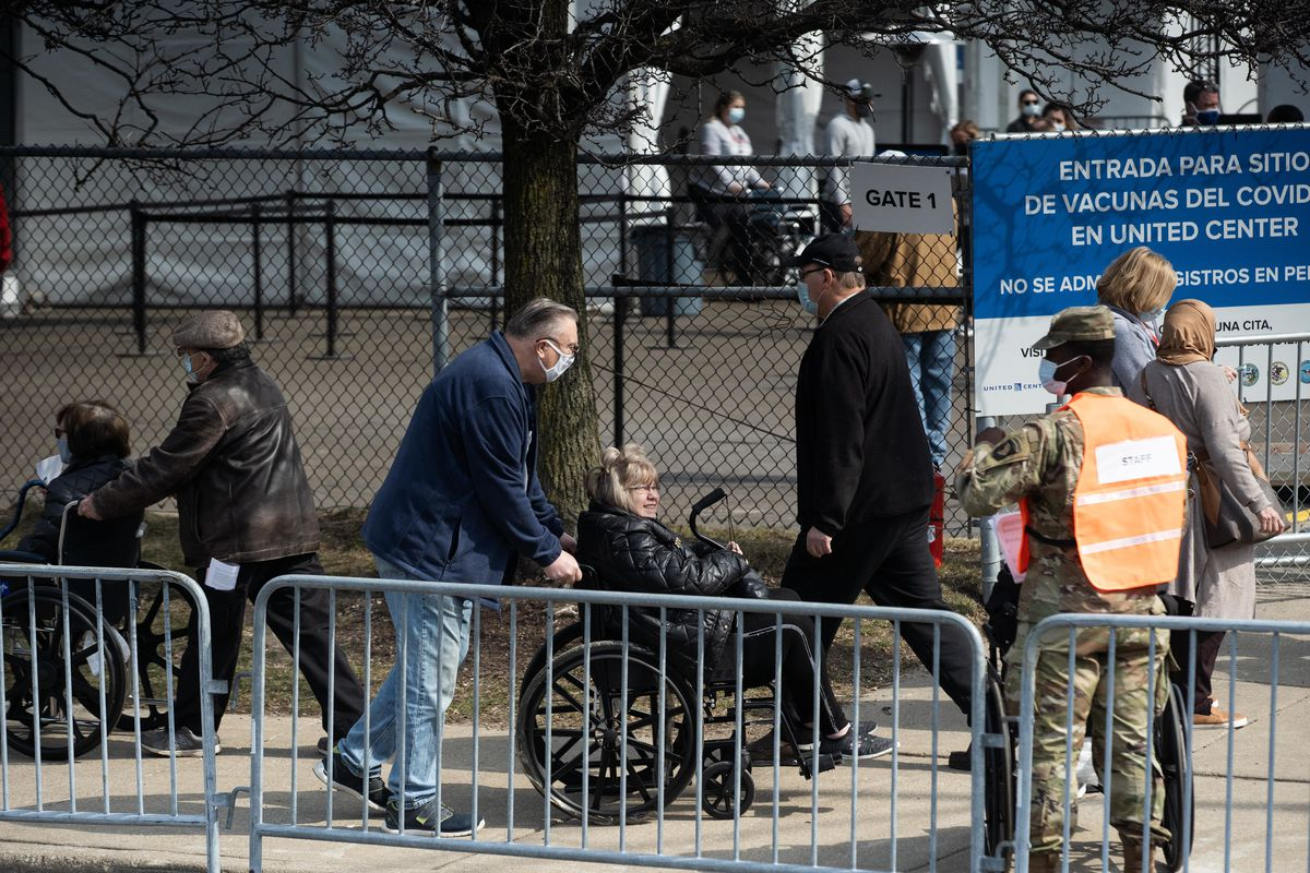 People walk outside the COVID-19 mass vaccination site that was set up on the parking lot of the United Center during the site's launch Tuesday.