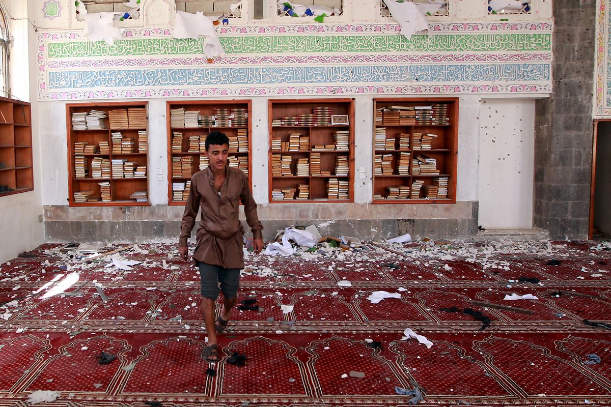 A Yemeni man looks over the damage to a mosque attacked by suicide bombers