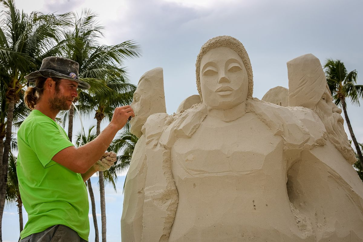 A man is sculpting his sand art installation in Key West.